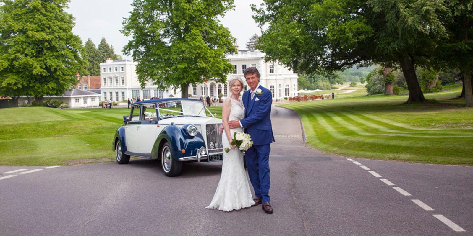 Burhill wedding couple on driveway with car