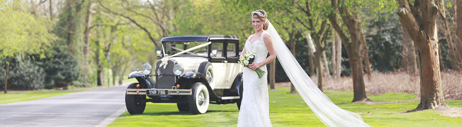 Bride posing in front of vintage car