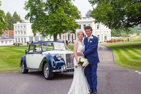 Burhill wedding couple in front of clubhouse with vintage car